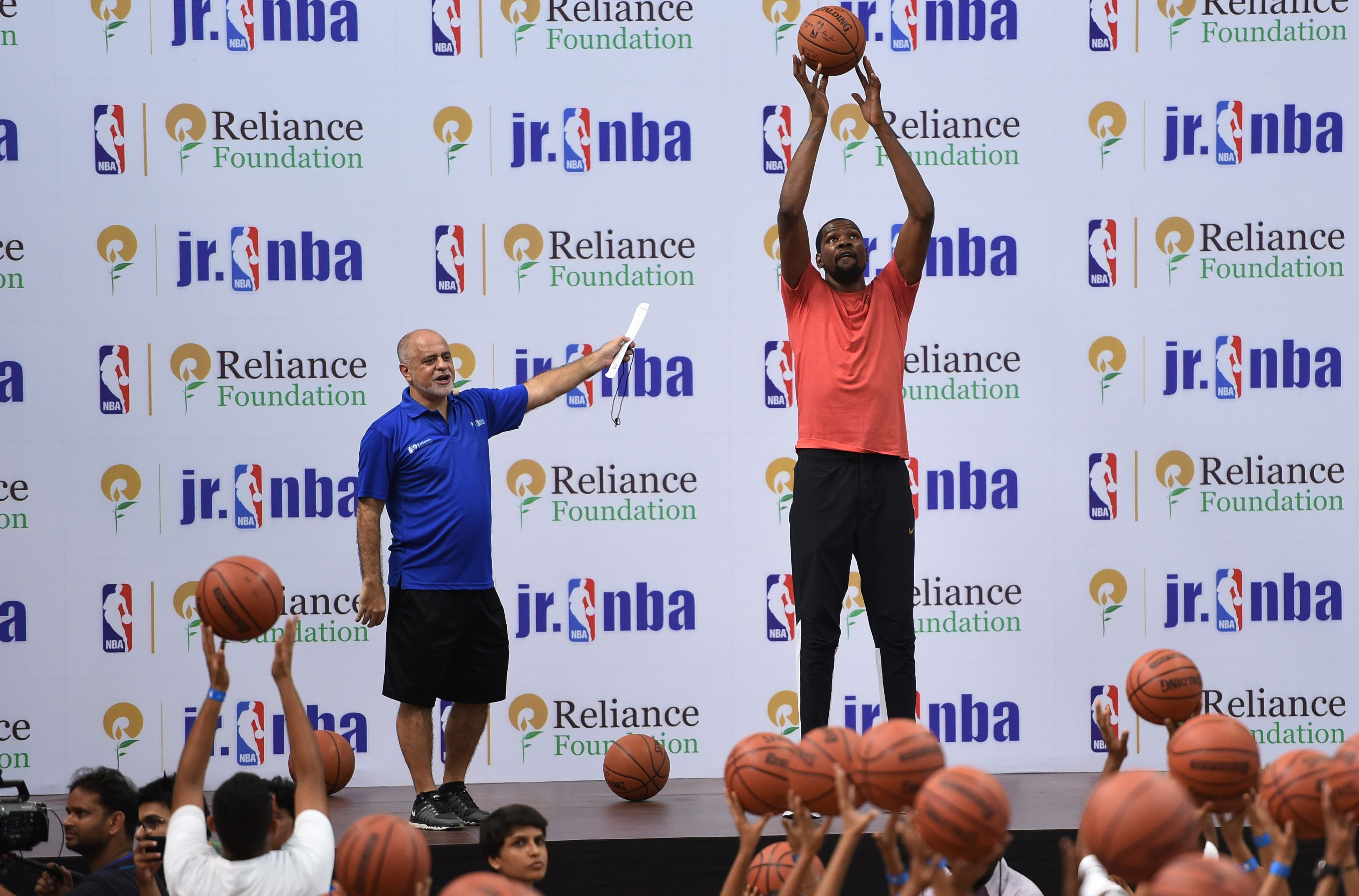 American basketball player for Golden State Warriors Kevin Durant (R) gives tips to children during an event at the NBA academy in Greater Noida, a suburb of New Delhi on July 28, 2017. / AFP PHOTO / MONEY SHARMA
