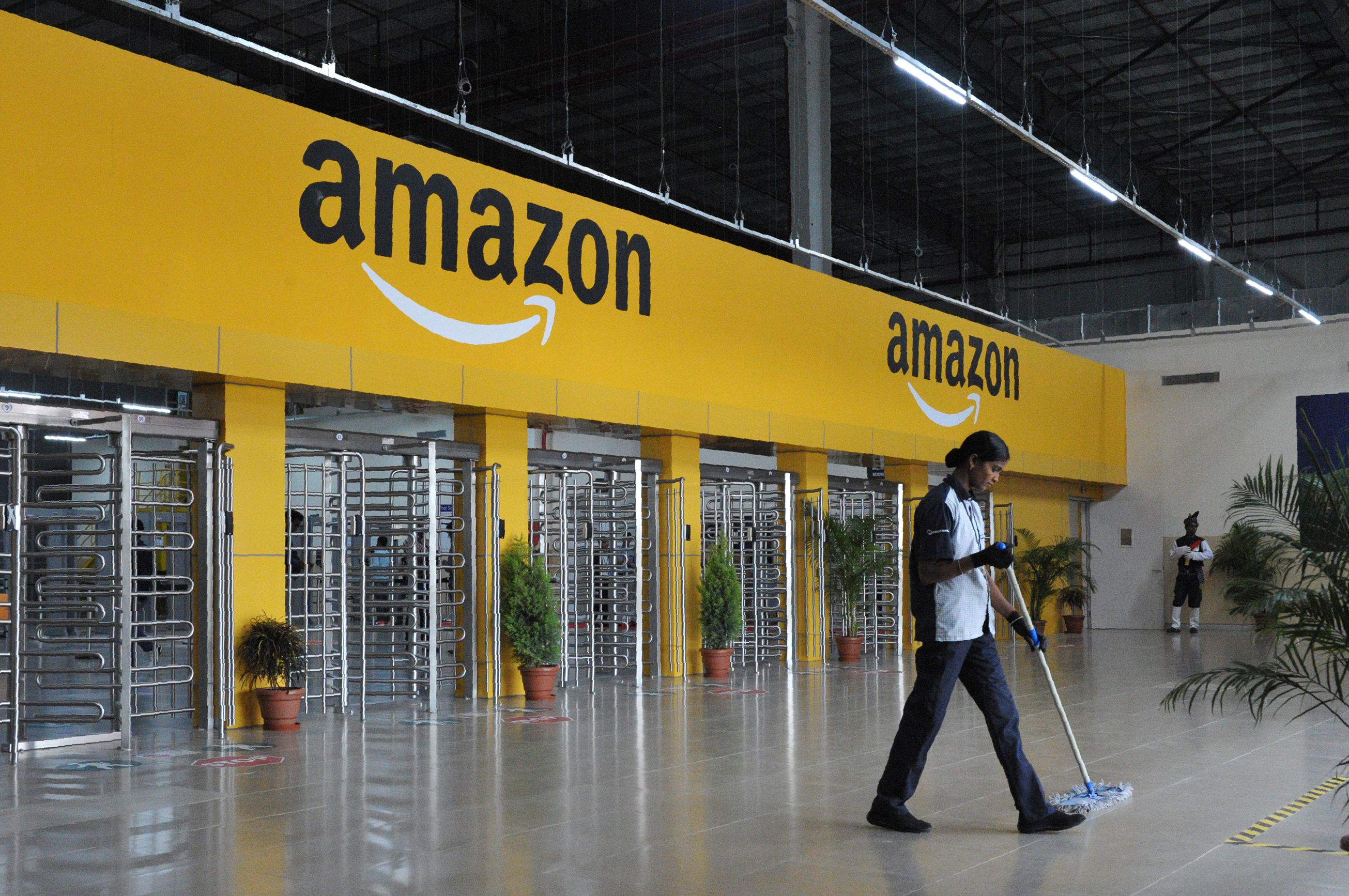 FILE PHOTO: An Indian employee cleans the floor inside Amazon's largest Fulfillment Centre (FC) in India, on the outskirts of Hyderabad.  (AFP PHOTO / NOAH SEELAM)