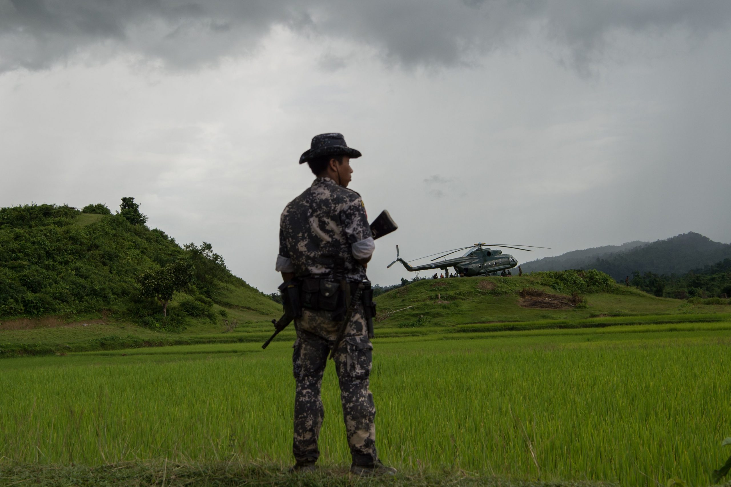 TOPSHOT - In this picture taken on September 27, 2017, a policeman stands guard near a military transport helicopter at Ye Baw Kyaw village, Maungdaw in Myanmar's northern Rakhine state. Rohingya militants on September 27 denied the Myanmar army's allegations that they had massacred scores of Hindu villagers, whose bodies soldiers displayed to the press after exhuming them from mass graves in northern Rakhine state. Major clashes between the army and the Muslim insurgents erupted last month, triggering a dire refugee crisis with nearly half a million Rohingya fleeing across the border to Bangladesh. / AFP PHOTO / STR        (Photo credit should read STR/AFP/Getty Images)