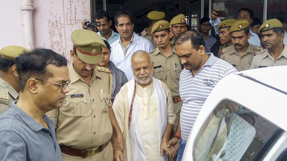 Swami Chinmayanand is led away by police