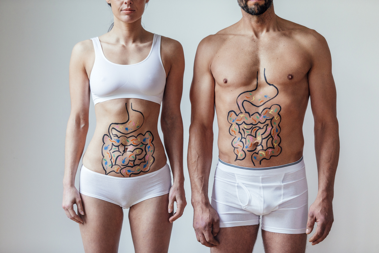 Female and  with an illustration on their abdomen of intestines with colourful bacteria. Beneficial gut microbiome