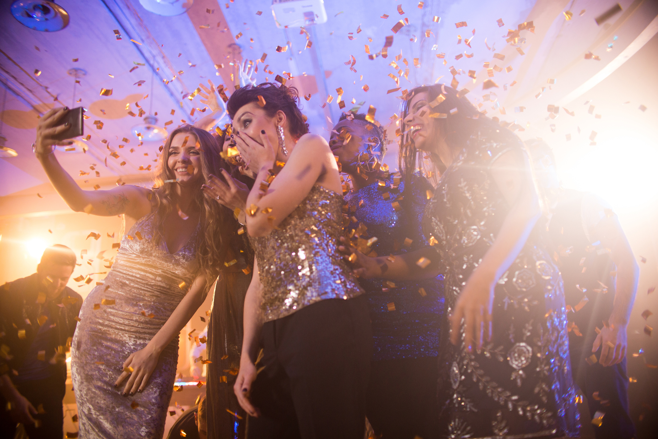 Group  of beautiful young women wearing glittering dresses dancing under golden confetti and taking selfies enjoying raving party in nightclub