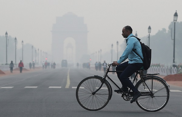 A man rides a cycle past the India Gate on a smoggy morning in New Delhi, India, October 28, 2019 (REUTERS/Adnan Abidi).