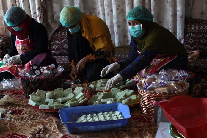 In this photo taken on October 8, 2019, Afghan female workers arrange bars of soap at an organic skin care company in Kabul. — AFP pic