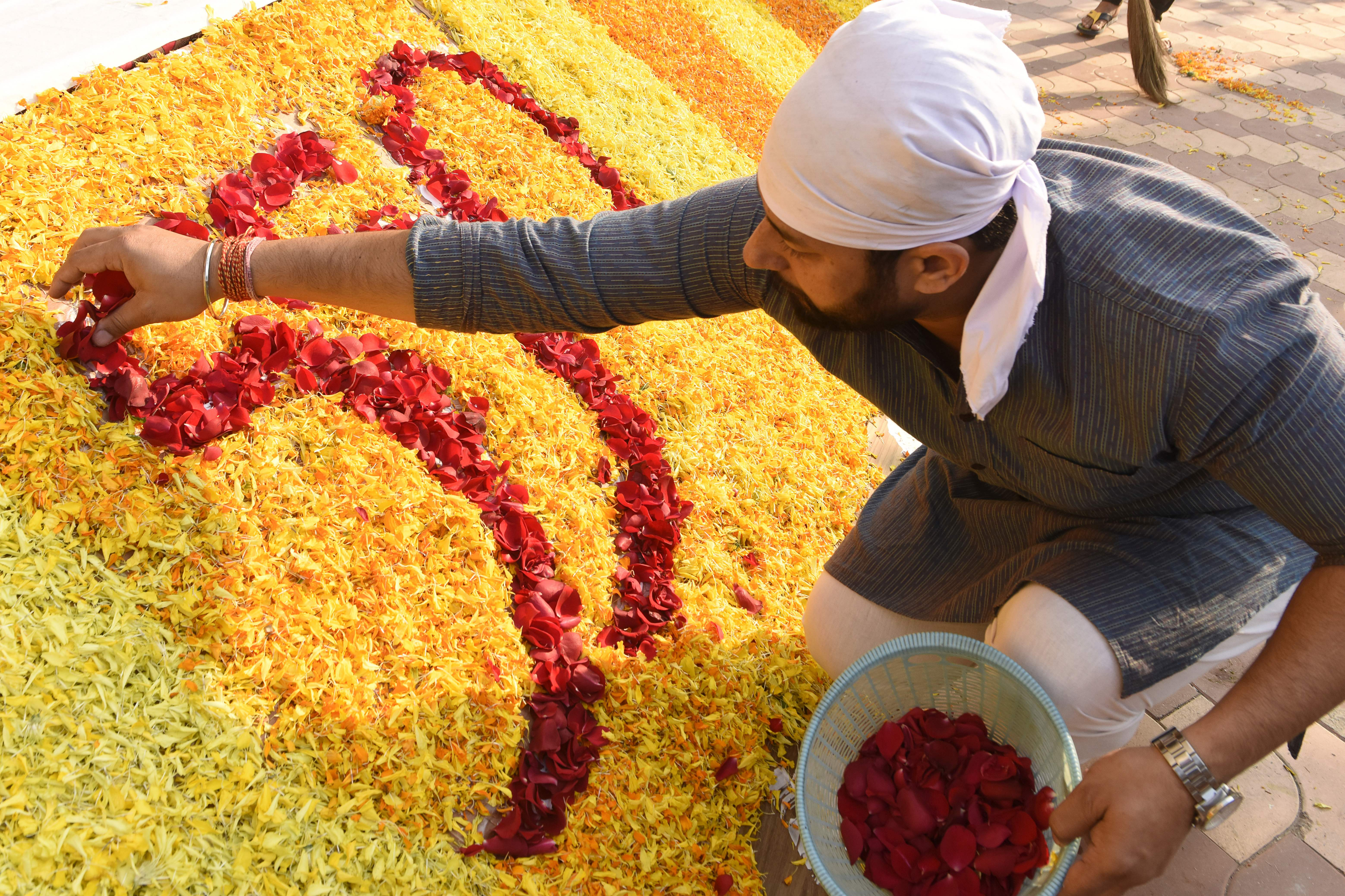 A Sikh devotee uses flower petals for decorations during a religious function ahead of 550th birth anniversary of Guru Nanak Dev ji, in Amritsar on November 10, 2019. (Photo by NARINDER NANU / AFP)