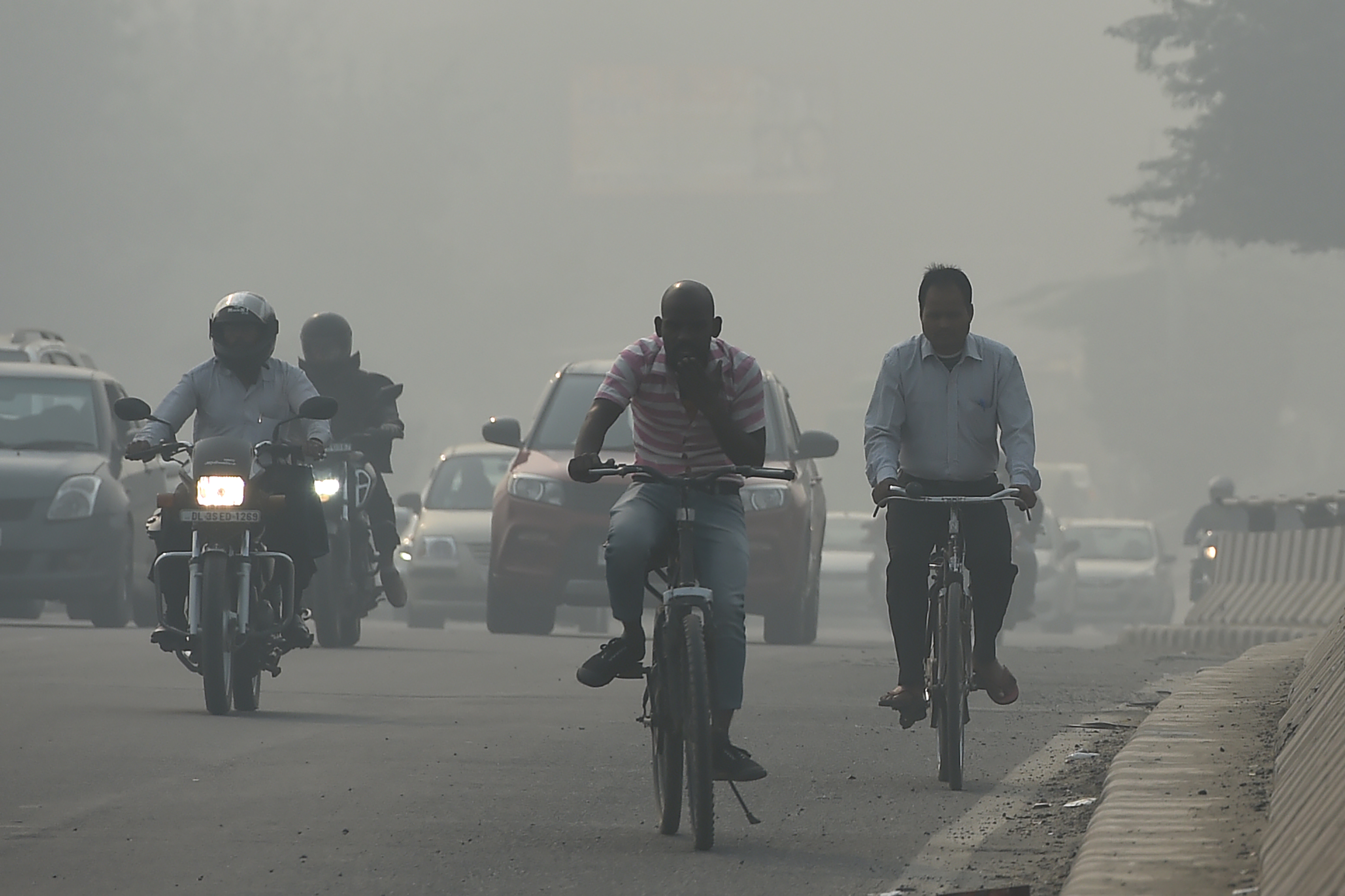 Drivers and cyclists make their way along a road under heavy smog conditions in New Delhi on November 12, 2019. (Photo by MONEY SHARMA/AFP via Getty Images)