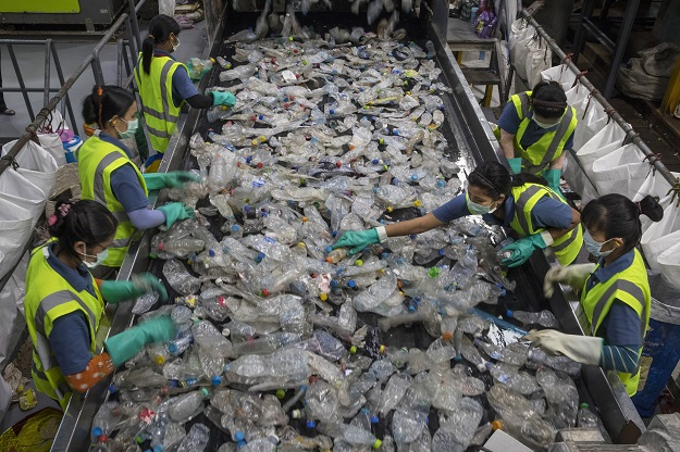 FILE PHOTO: At the Indorama Ventures factory, flattened plastic bottles that have been steam cleaned are sorted by factory employees as they move along on a conveyer belt for processing (Photo: Paula Bronstein/Getty Images).