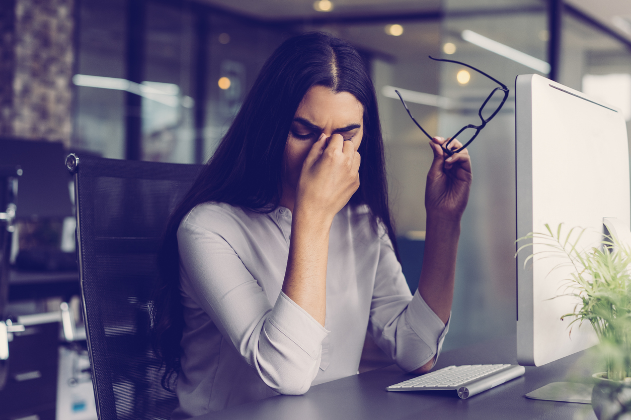 Portrait of depressed young Latin-American businesswoman sitting at computer in office holding glasses and rubbing eyes. Overworking concept