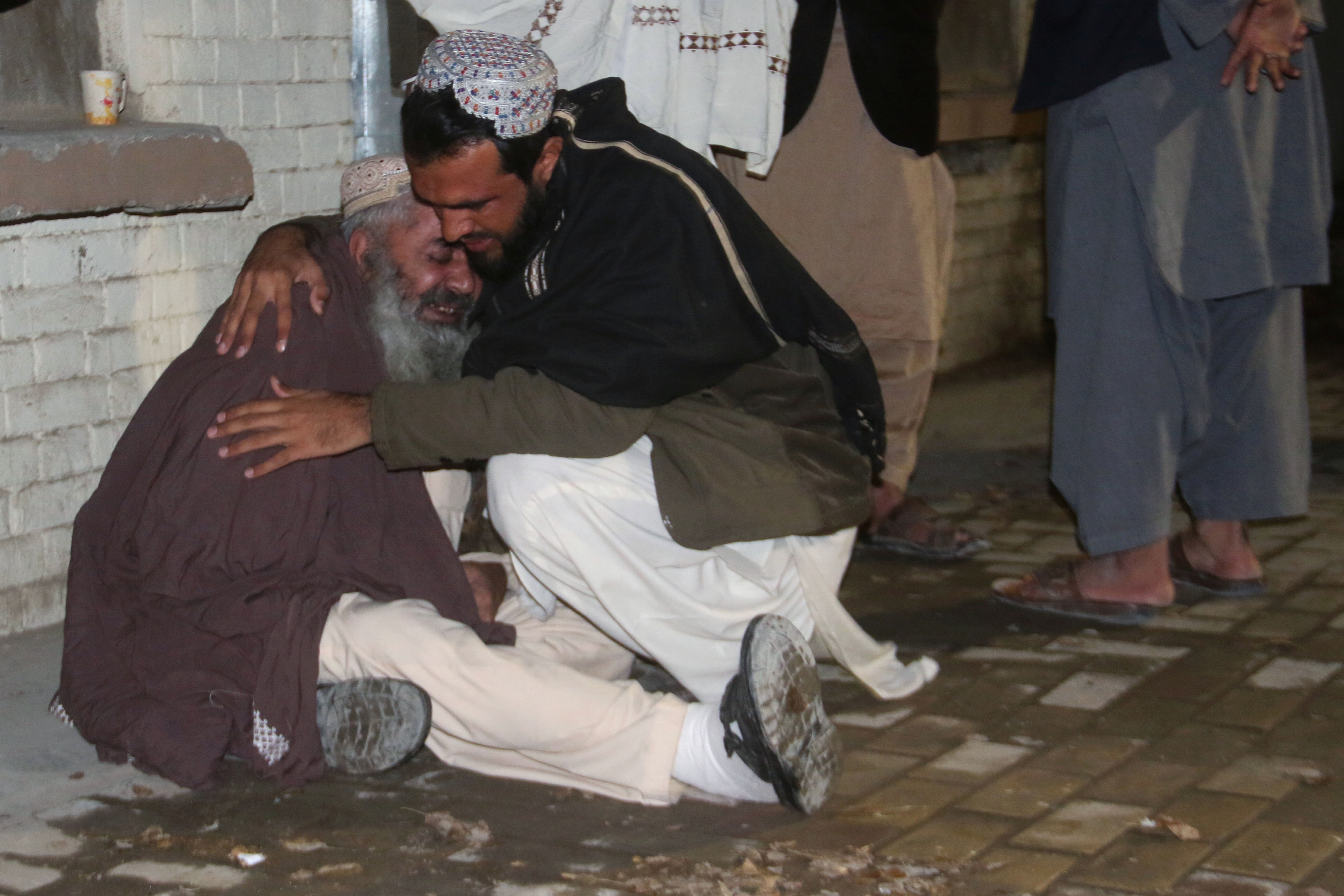 Men comfort each other as they mourn the death of a relative who was killed in a bomb blast in a mosque, at a hospital morgue in Quetta, Pakistan January 10, 2020. REUTERS/Naseer Ahmed