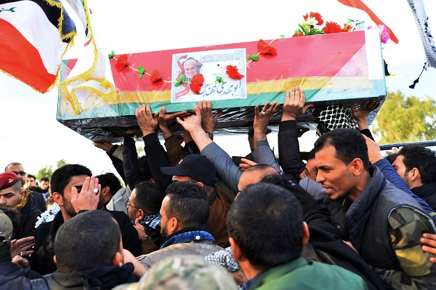 Members of Iraq's Hashed al-Shaabi paramilitary network carry the coffin of their slain chief Abu Mahdi al-Muhandis, ahead of his burial on January 8. Muhandis was killed last week with Iran's top military chief Qasem Soleimani and eight others in a US drone attack near Baghdad airport. (Photo: HAIDAR HAMDANI/AFP via Getty Images).