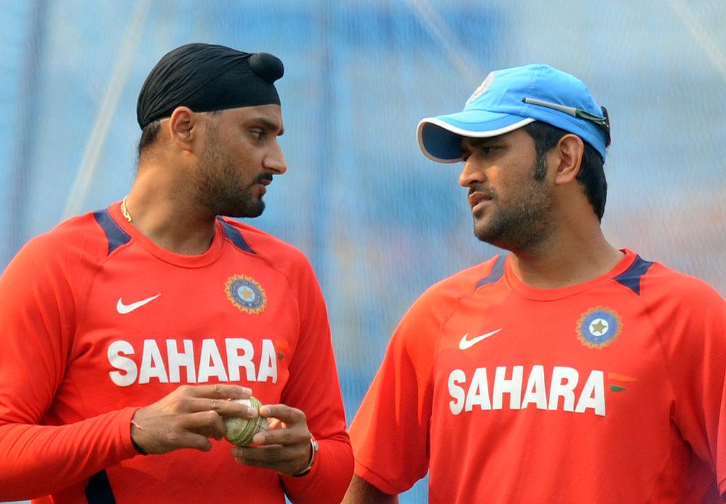 Indian cricketers Harbhajan Singh (L) talks with  Mahendra Singh Dhoni (INDRANIL MUKHERJEE/AFP via Getty Images)