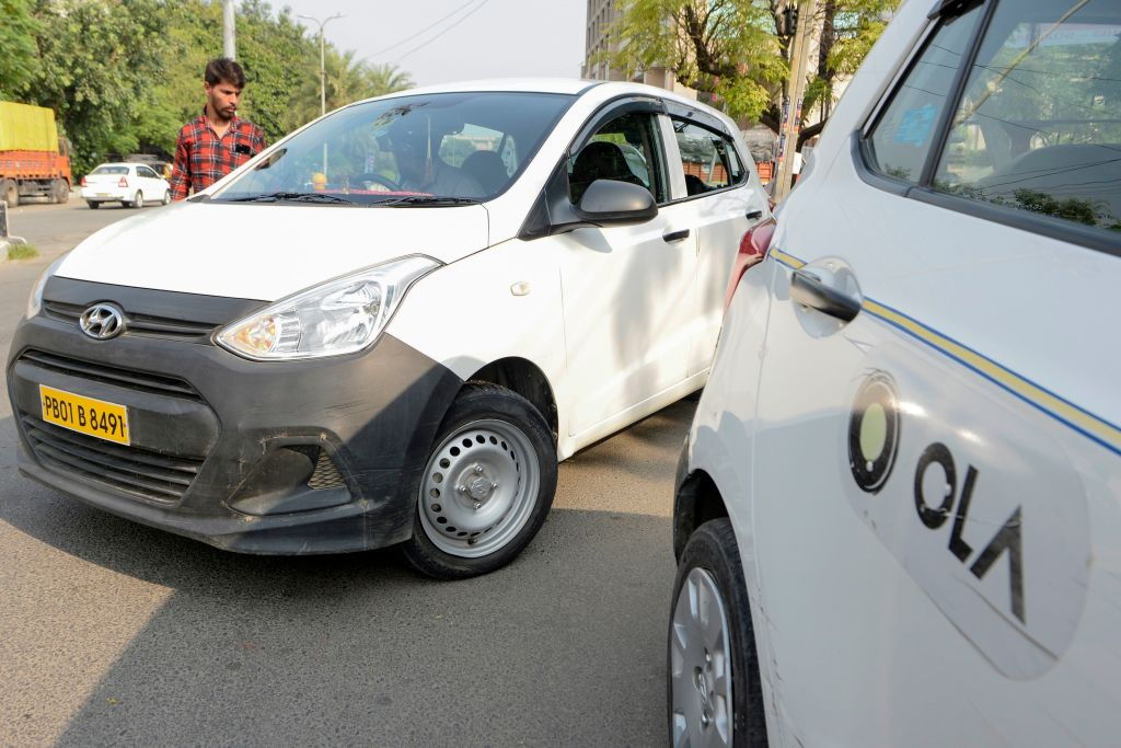 In this photograph taken on September 12, 2019, an Ola cab driver picks up a passenger at a roadside in Amritsar. - When India's Finance Minister Nirmala Sitharaman September 10 claimed millennials' preference for ride-hailing apps was contributing to a painful slump in car sales, it sparked a online backlash from furious youngsters. While data shows ride-hailing firms such as Uber and Ola are popular with younger consumers more comfortable with shared mobility and digital trends, analysts say the auto industry's problems run deeper than that -- and it is facing more serious bumps in the road. (Photo by NARINDER NANU / AFP) / TO GO WITH 'INDIA-TRANSPORT-AUTOMOBILE-ECONOMY', FOCUS BYGLENDA KWEK WITH ARCHANA THIYAGARAJAN        (Photo credit should read NARINDER NANU/AFP via Getty Images)