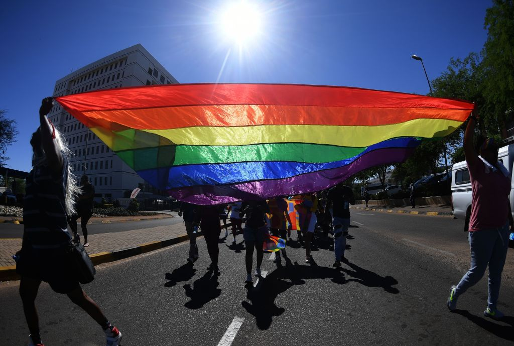 Members and supporters of the lesbian, gay, bisexual, transgender (LGBT) hold a rainbow flag as they take part in the first Botswana Pride Parade in Gaborone, on November 30, 2019. - The parade aiming to achieve greater tolerance and inclusion of all African LGBTQ+ identities is the first one organised in Botswana, after the Court ruled on June 11 in favour of decriminalising homosexuality, which had been punishable by a jail term of up to seven years. (Photo by Monirul Bhuiyan / AFP) (Photo by MONIRUL BHUIYAN/AFP via Getty Images)