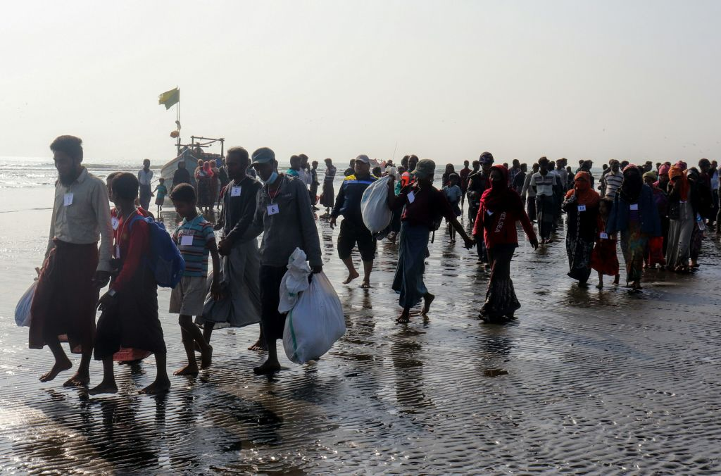 Rohingya people who were arrested at sea in December walk on a beach after being transported by Myanmar authorities to Thalchaung near Sittwe in Rakhine state on January 13, 2020.  (Photo by STR/AFP via Getty Images)