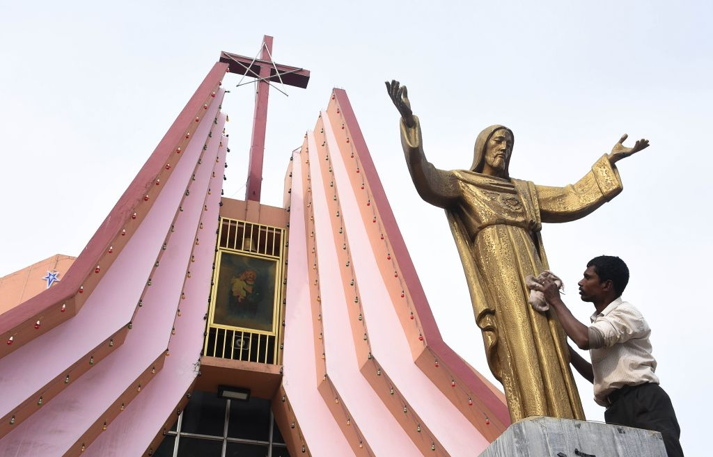 An Indian worker cleans the statue of Jesus Christ at St Joseph's Church in Guwahati on December 19, 2017. (BIJU BORO/AFP via Getty Images)