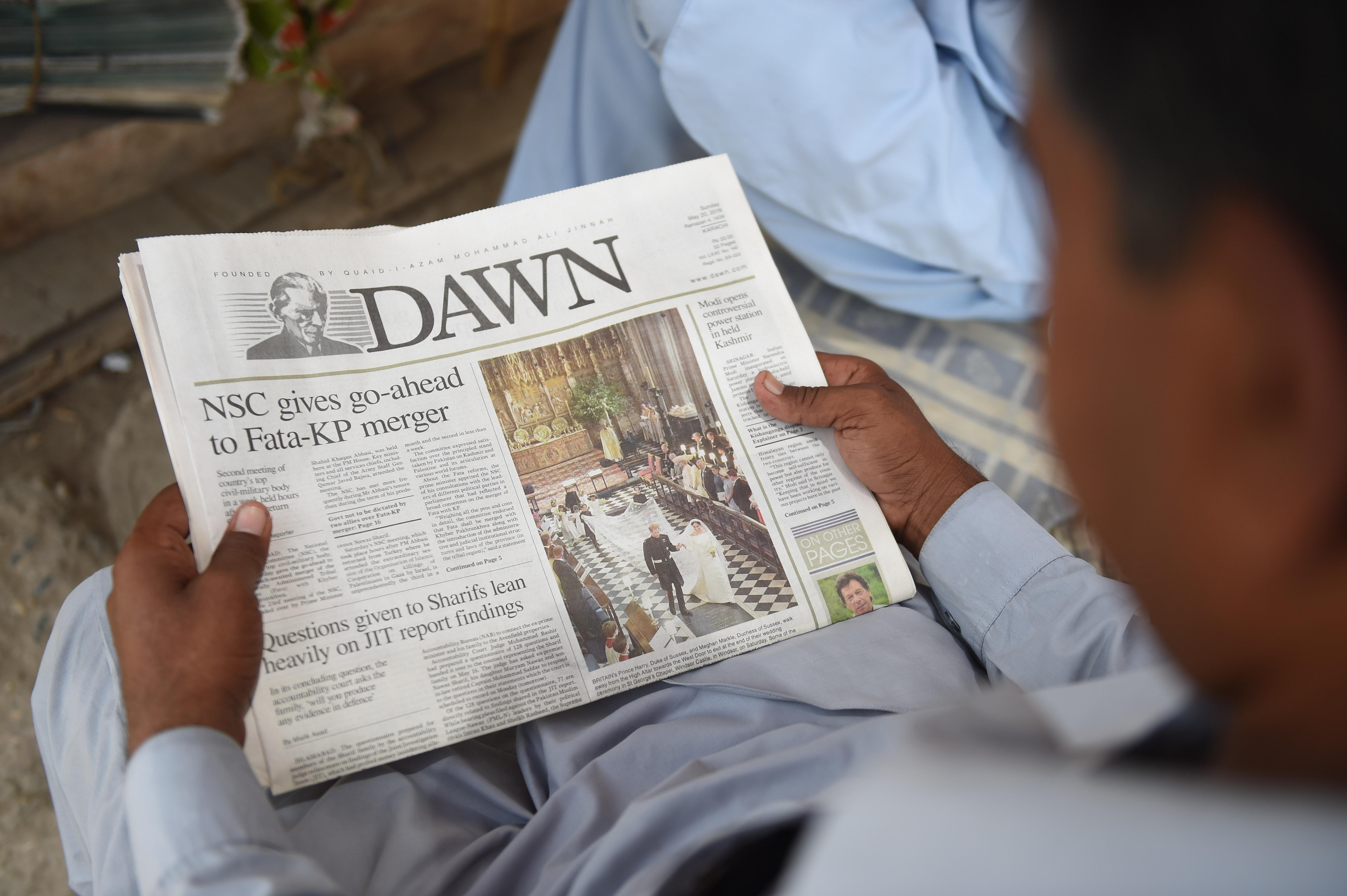 A Pakistan man reads a copy of the Dawn English-language newspaper. (Photo by RIZWAN TABASSUM / AFP)