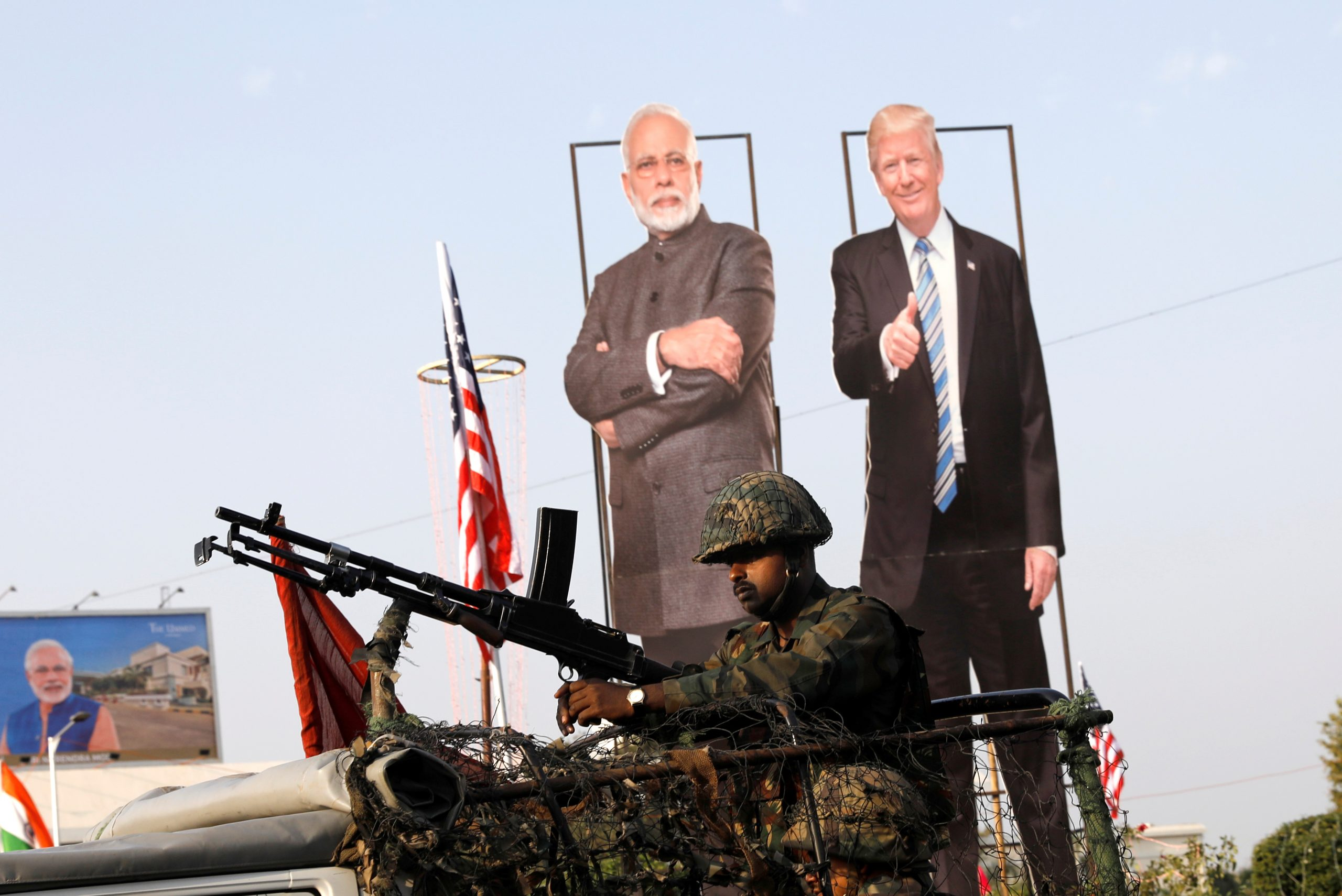 An Indian soldier keeping vigil atop an armoured vehicle next to cutouts of Indian Prime Minister Narendra Modi and US President Donald Trump in Ahmedabad, Gujarat. Trump's India visit starts on Monday (24). (Photo: Reuters/Adnan Abidi)