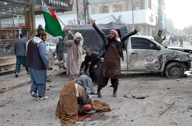 People react as a wounded man sits on the ground after a bomb blast in Quetta, Pakistan February 17, 2020 (Photo: REUTERS/Naseer Ahmed).