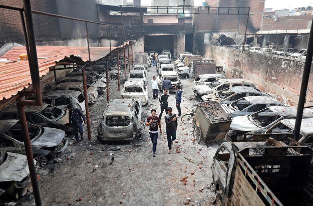 Men look at burnt vehicles at a parking lot in a riot affected area following clashes between people demonstrating for and against a new citizenship law in New Delhi on February 27, 2020 (REUTERS/Rupak De Chowdhuri).