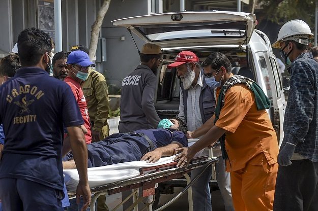 Paramedics personnel shift a patient on a stretcher into the hospital in Karachi on February 18, 2020, after a toxic gas leak (Photo: RIZWAN TABASSUM/AFP via Getty Images).