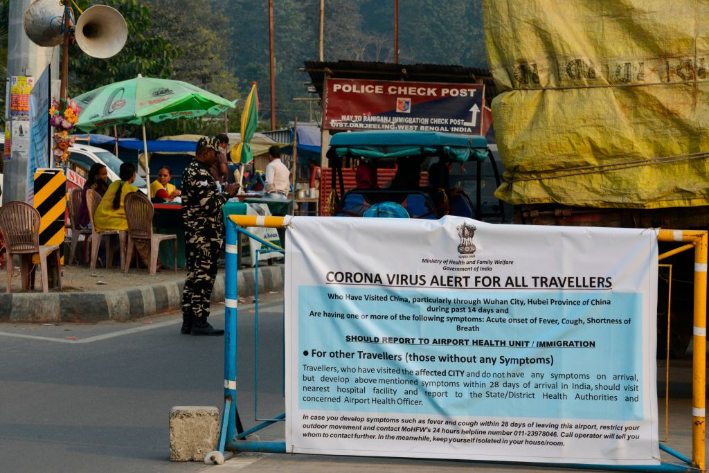 A banner placed by Indian health workers is seen during a Corona virus informarion camp for travellers at an India-Nepal border crossing, some 32 kms from Siliguri (Photo by DIPTENDU DUTTA/AFP via Getty Images)