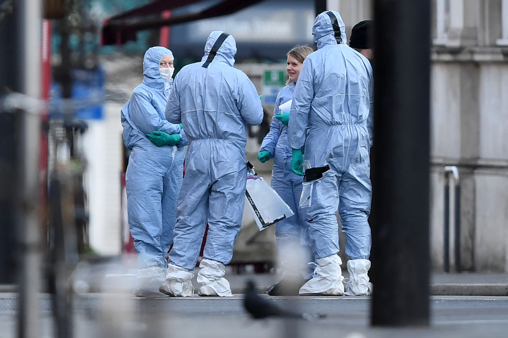 """Police forensic officers work on Streatham High Road in south London on February 3, 2020, after a man was shot dead by police on February 2, following reports of people being stabbed in the street. - A man wearing a """"hoax device"""" shot dead by police in London Sunday after stabbing two people had recently been released from prison for previous terrorism offences, British media reported. The suspect was released last month after serving around half of an approximate three-year sentence for disseminating terrorist material, according to multiple reports. (Photo by DANIEL LEAL-OLIVAS / AFP)"""