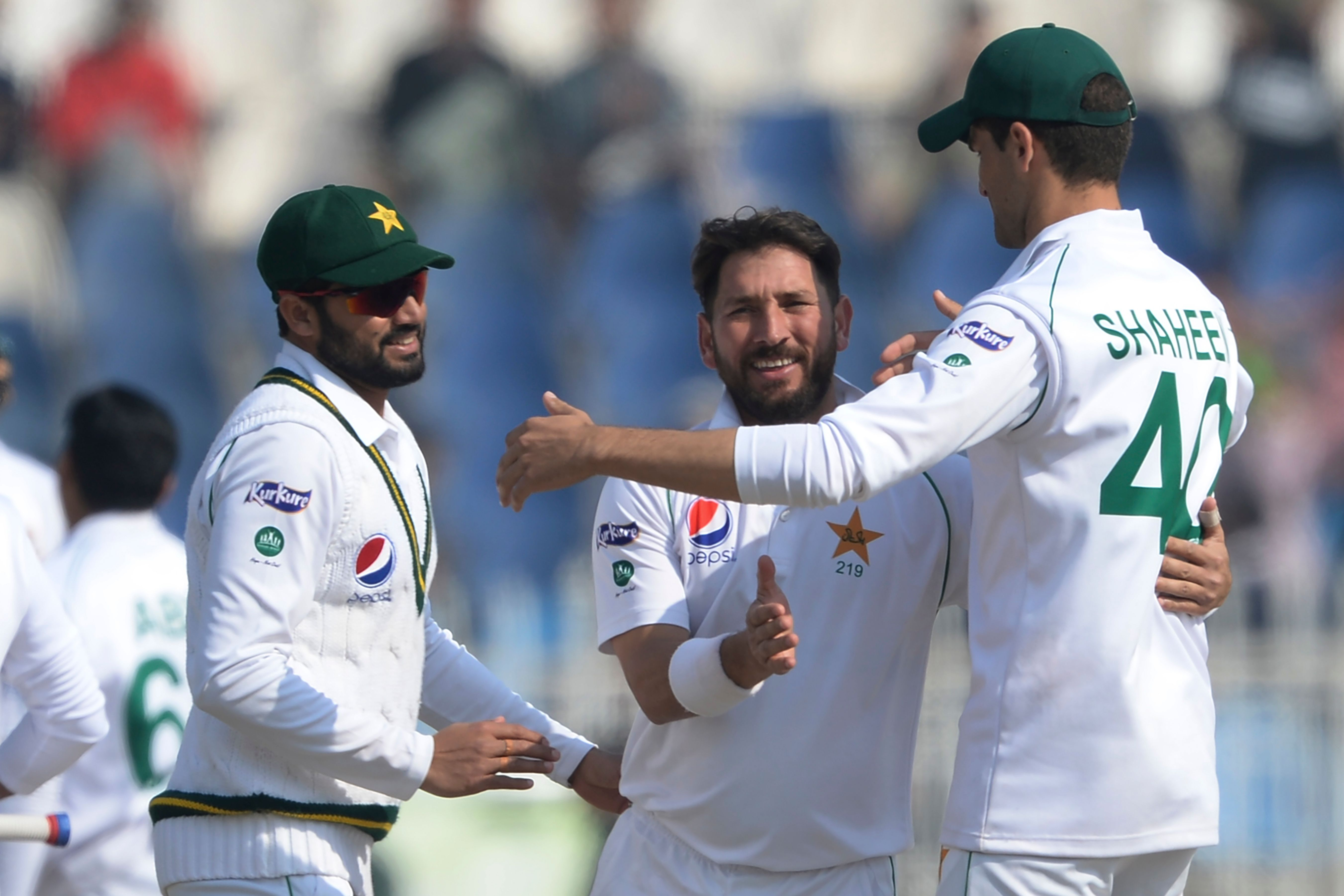 Pakistan's bowler Yasir Shah (C) celebrates with captain Azhar Ali (L) and Shaheen Shah Afridi after taking last wicket of Bangladesh's Abu Jayed during the fourth day of the first cricket Test match between Pakistan and Bangladesh at the Rawalpindi Cricket Stadium in Rawalpindi on February 10, 2020. - Pakistan completed a crushing innings and 44-run victory over Bangladesh. (Photo by AAMIR QURESHI/AFP via Getty Images)
