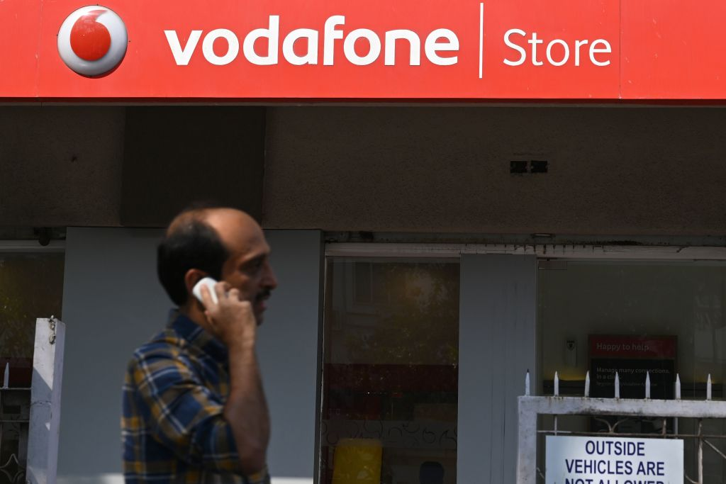 A pedestrian uses his phone while walking past a Vodafone store in Mumbai on February 18, 2020. Shares of Vodafone Idea on February 18 tanked over 16 per cent on the Bombay Stock Exchange (BSE) due to rating downgrade on AGR dues and other issues of the company. (Photo by PUNIT PARANJPE/AFP via Getty Images)