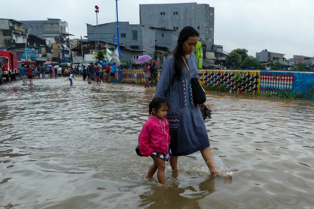 A woman and her daughter walk through a flooded road after heavy rain in Jakarta on February 25, 2020.  Dozens of Jakarta neighbourhoods were flooded after torrential rains pounded Indonesia's capital, less than two months after nearly 70 people were killed in some of the megacity's worst flooding in years. (Photo: BAY ISMOYO/AFP via Getty Images)
