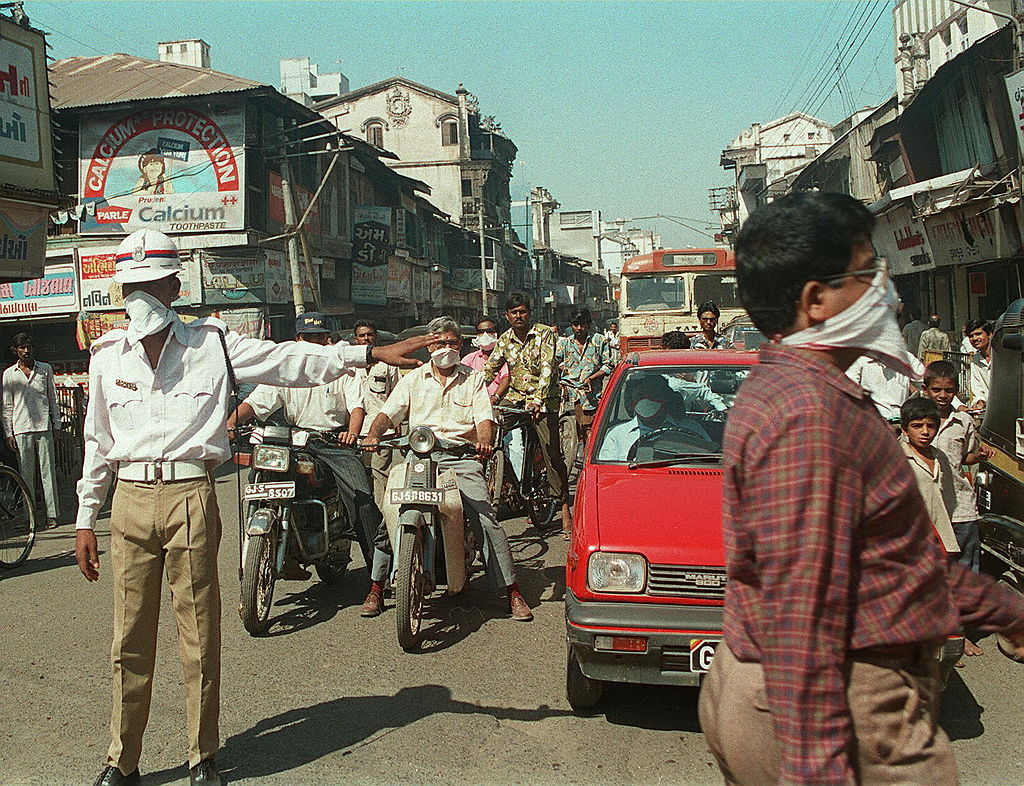 FILE PHOTO: A policeman shown in file photo dated 30 September 1994 directing traffic in Surat with his mouth and nose covered during the plague outbreak. (Photo RAVEENDRAN/AFP via Getty Images)