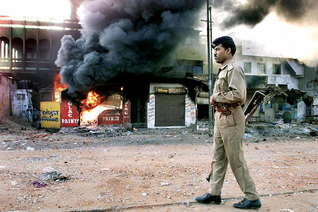 AHMEDABAD, INDIA:  (FILES) In this picture taken 01 March 2002, An Indian policeman looks on as a row of shops burns in Ahmedabad.  Top police official  R. B. Sreekumar in an explosive testimony has said the anti-Muslim riots that raged in India's Gujarat state two years ago was backed by its ruling Hindu nationalist government, officials reported 18 August 2004. The 172-page testimony was unveiled a day after India's Supreme Court Tuesday reopened 2,000 cases from the riots which claimed the lives of more than 2,000 people, mostly Muslims, in the western Indian state. AFP PHOTO/STR  (Photo credit should read STR/AFP via Getty Images)