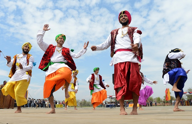Indian Border Security Force Soldiers (BSF) dance as they celebrate during the Holi festival inside a camp in Srinagar on March 27, 2013.  Holi, also called the Festival of Colours, is a popular Hindu spring festival observed in India at the end of the winter season on the last full moon day of the lunar month. AFP PHOTO/Tauseef MUSTAFA        (Photo credit should read TAUSEEF MUSTAFA/AFP via Getty Images)