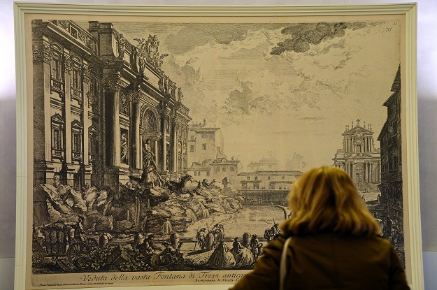 A visitor looks at a print of an engraving by Italian artist Piranesi showing the Trevi fountain (Photo: GABRIEL BOUYS/AFP via Getty Images).