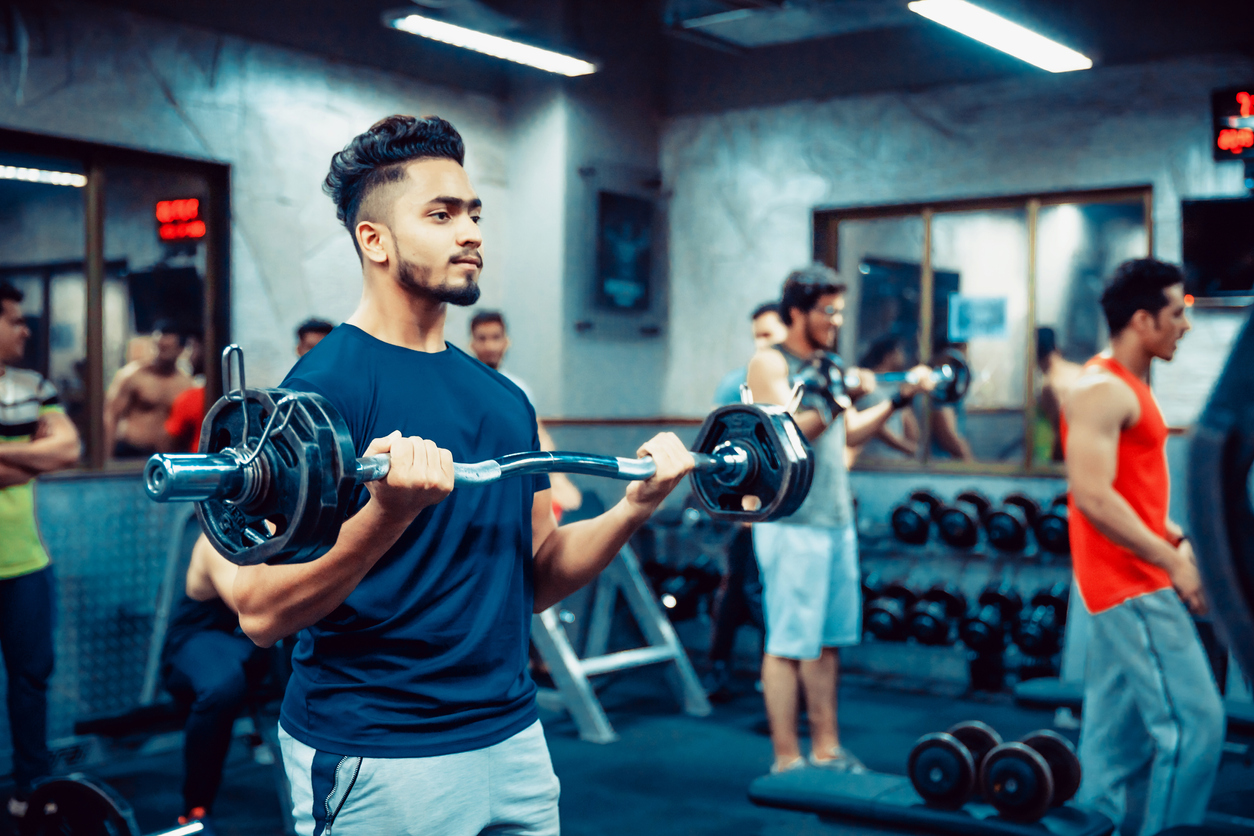 India, Fitness, Healthy Lifestyle - Indian man lifting weights at a fitness centre
