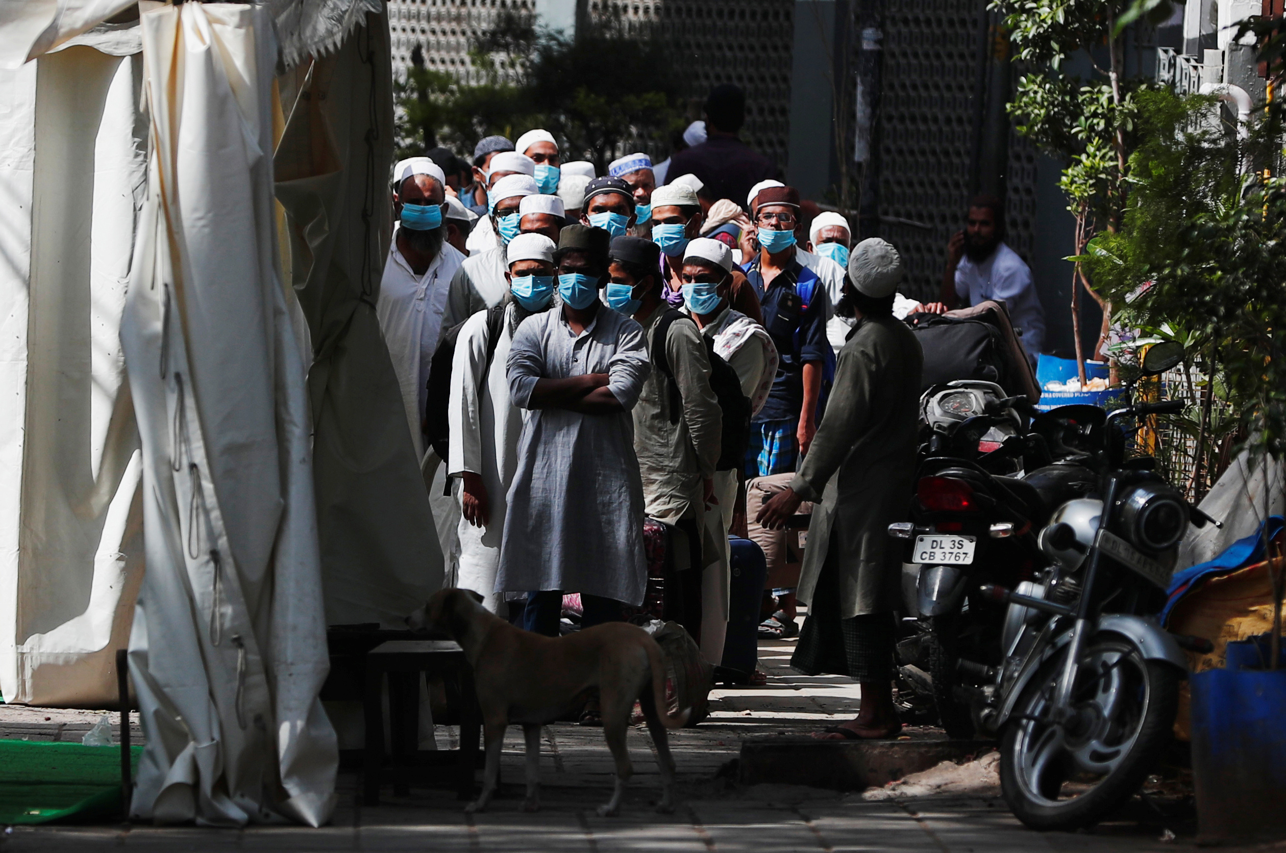 Men wearing protective masks wait for a bus that will take them to a quarantine facility, amid concerns about the spread of coronavirus disease (COVID-19), in Nizamuddin area of New Delhi, India, March 31, 2020. (REUTERS/Adnan Abidi)