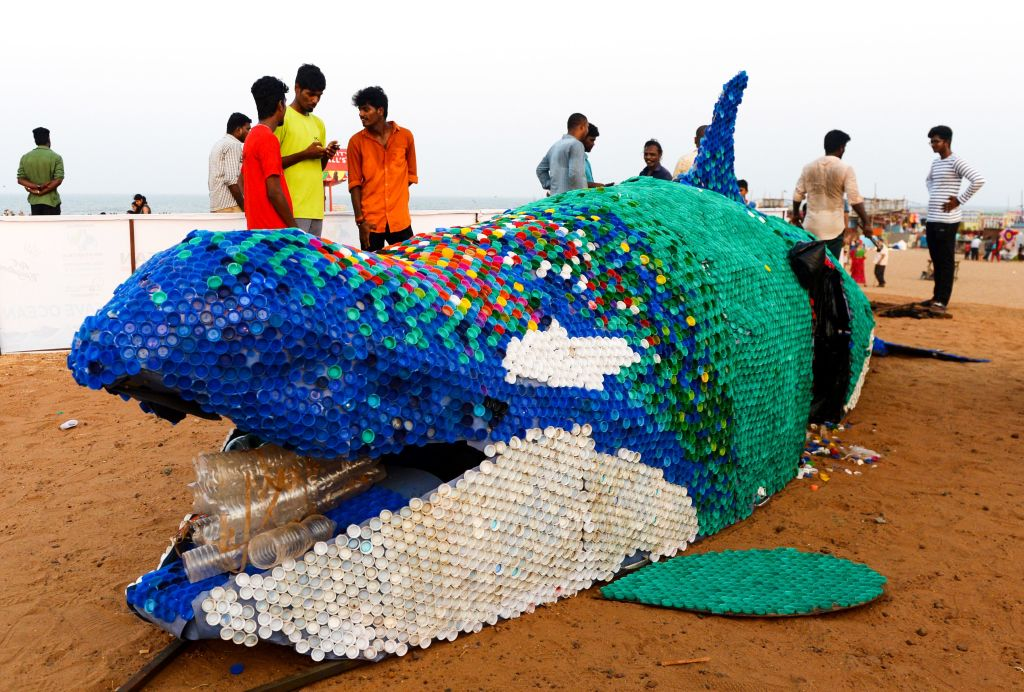 File photo of people walking past a large-scale sculpture of a killer whale made of single use plastic and 40,000 plastic bottle caps being displayed to raise awareness on ocean contamination at Elliot's beach in Chennai. The UNEP has praised India's efforts in the global Clean Seas campaign. (Photo: ARUN SANKAR/AFP via Getty Images)