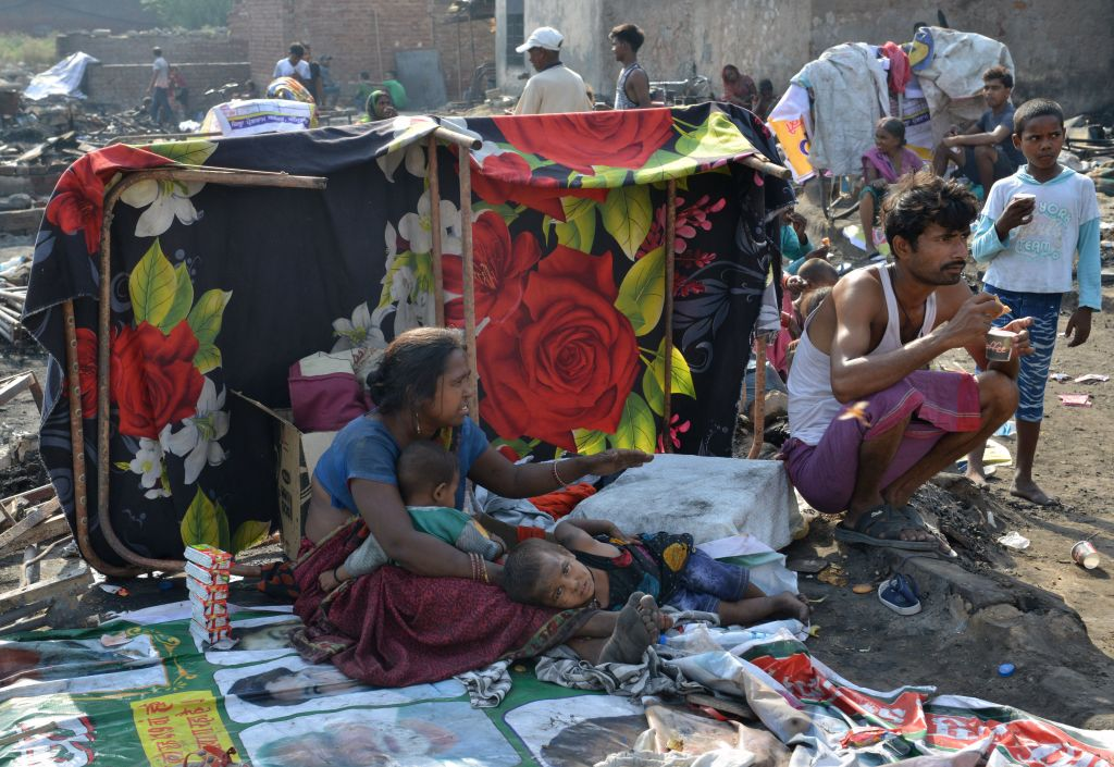 An Indian family sit together next to their surviving belongings a day after a fire that destroyed dwellings in a slum area in Amritsar on June 28, 2019. - No casualties were reported in the blaze that destroyed hundred of settlements in the slum area, the cause of which was still being investigated. (Photo by NARINDER NANU / AFP)        (Photo credit should read NARINDER NANU/AFP via Getty Images)
