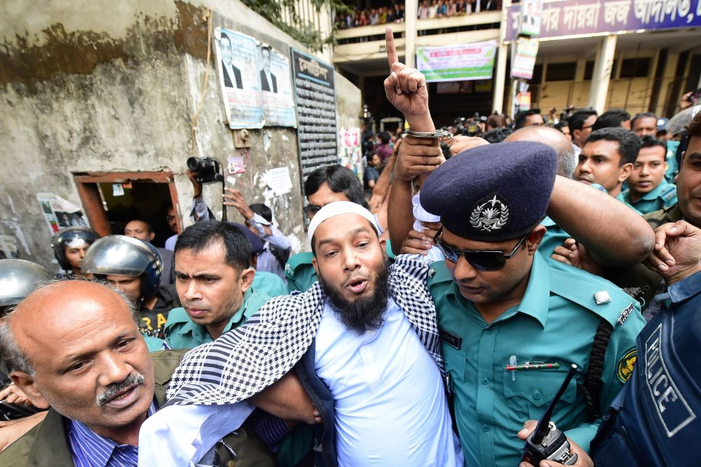 Police escort an Islamist extremist (C) to a prison van after his trial for allegedly plotting the Holey Artisan Bakery cafe attack, at a court in Dhaka on November 27, 2019. - Seven Islamist extremists have been sentenced to death by a Bangladesh court over a savage 2016 attack that killed 22 people including 18 foreigners at a Dhaka cafe popular with Westerners. (Photo by Munir UZ ZAMAN / AFP)