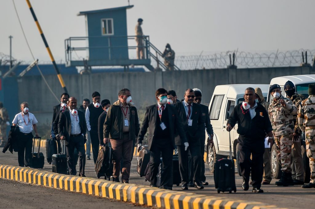 FILE PHOTO: Crew members and officials wearing protective facemasks carry their belongings at Indira Gandhi International Airport following the evacuation of Indian nationals from the Chinese city of Wuhan, in New Delhi. (Photo by MONEY SHARMA/AFP via Getty Images)