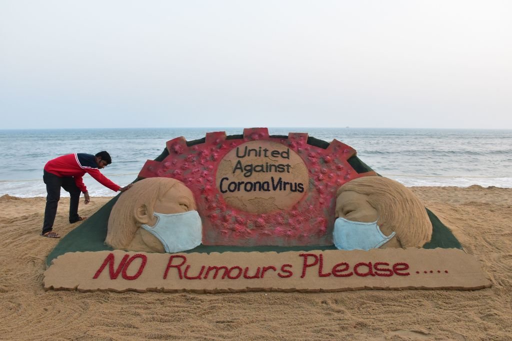 FILE PHOTO: Indian artist Sudarsan Pattnaik puts some final touches as he makes a sand sculpture depicting people wearing protective facemasks with a message reading 'United against corona virus' at Puri beach in Puri. (Photo by STR/AFP via Getty Images)