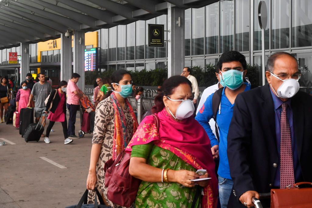 Passengers wearing facemasks as a preventive measure against the spread of the COVID-19 coronavirus outbreak, enter Netaji Subhas Chandra Bose International Airport in Kolkata on March 7, 2020. (Photo by DIBYANGSHU SARKAR/AFP via Getty Images)