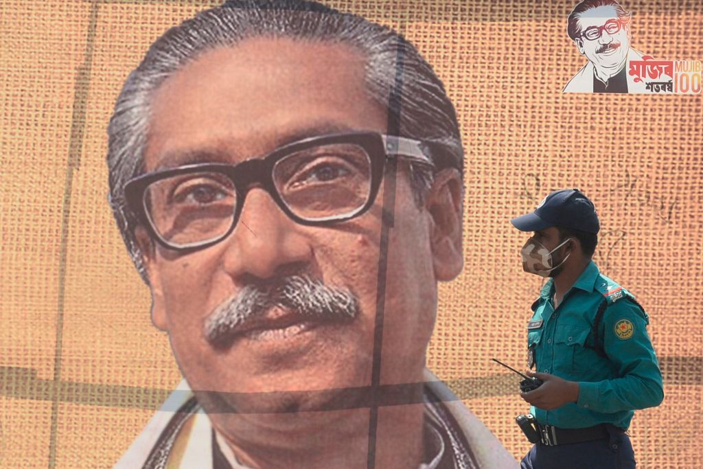 A policeman wearing a facemask amid fears of the spread of COVID-19 novel coronavirus, walks past a banner with a picture of Bangladeshs founder Sheikh Mujibur Rahman, in Dhaka on March 9, 2020. (Photo by MUNIR UZ ZAMAN/AFP via Getty Images)