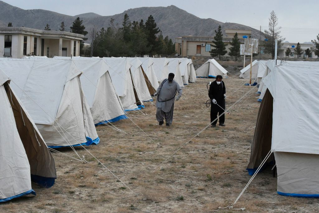 Workers of the Provincial Disaster Management Authority (PDMA) of Balochistan spray disinfectant on tents at a quarantine camp, prepared for people returning from Iran via the Pakistan-Iran border town of Taftan to prevent the spread the COVID-19 coronavirus, on the outskirts of Quetta on March 9, 2020.  (Photo by Banaras KHAN / AFP) (Photo by BANARAS KHAN/AFP via Getty Images)