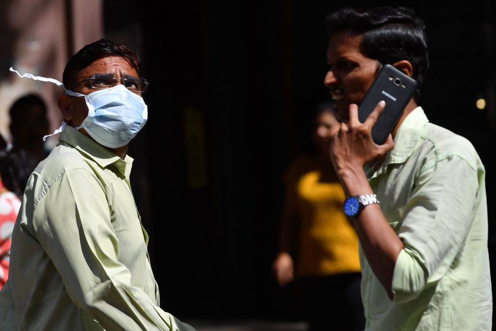 A man wearing a facemask amid concerns of the spread of the COVID-19 coronavirus, watches share prices on a digital display on the facade of the Bombay Stock Exchange (BSE) building in Mumbai on March 13, 2020. (Photo by INDRANIL MUKHERJEE/AFP via Getty Images)