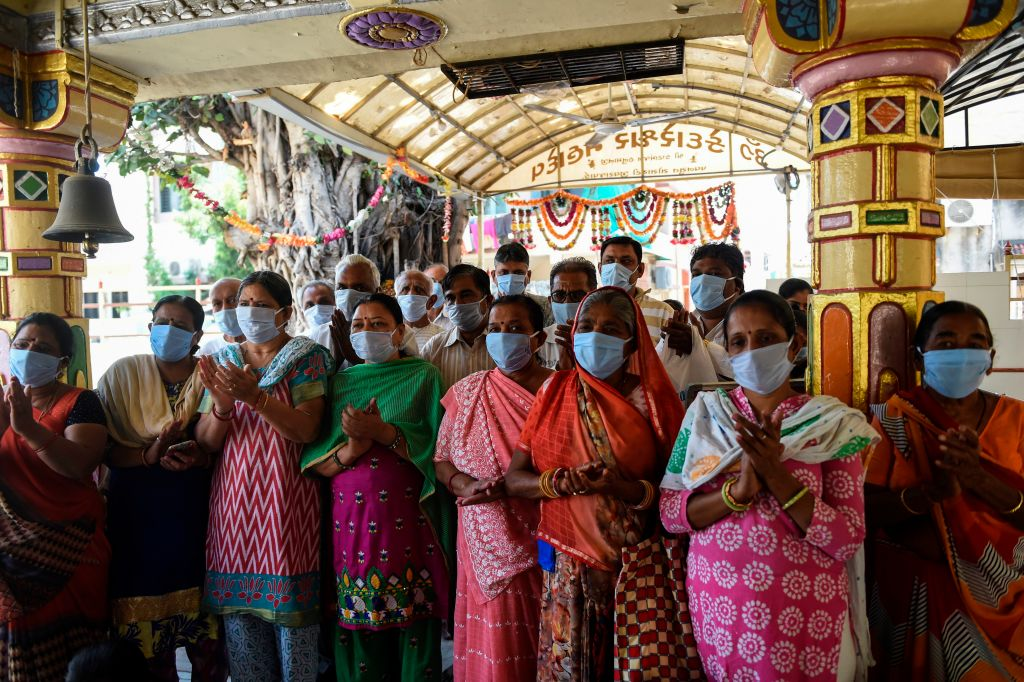 Hindu devotees wear facemasks amid concerns over the spread of the COVID-19 coronavirus as they pray at a Hanuman Temple in Ahmedabad on March 17, 2020. (Photo by SAM PANTHAKY/AFP via Getty Images)