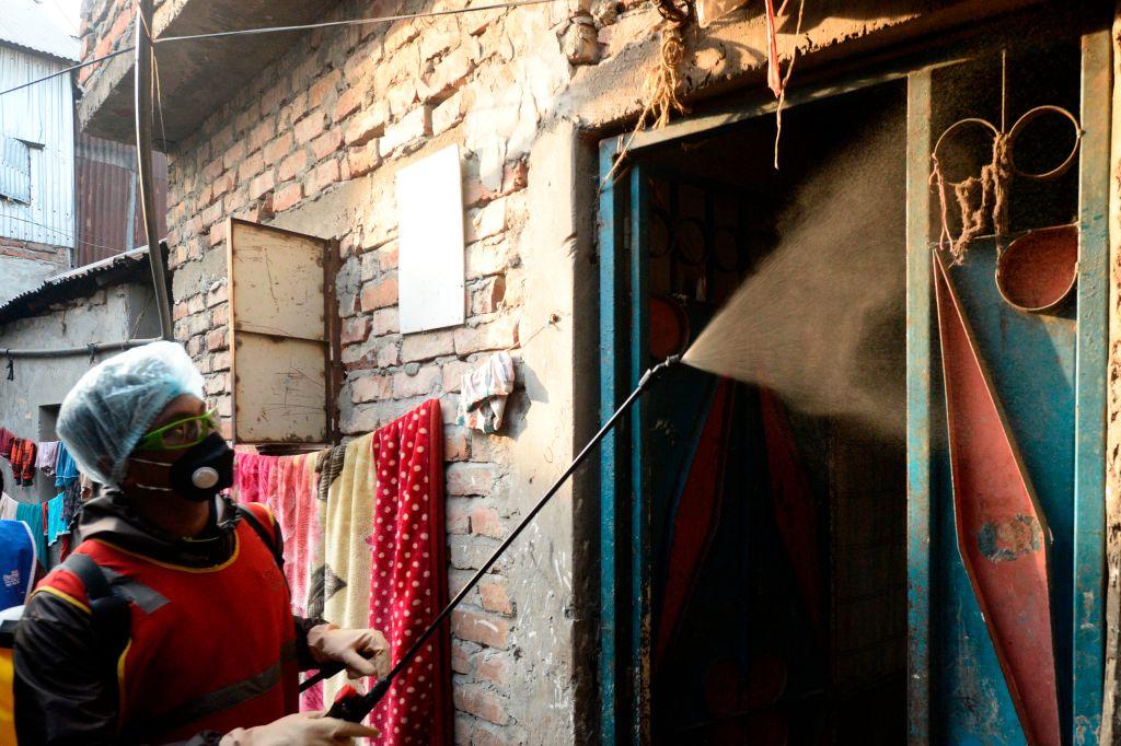A volunteer sprays disinfectant inside a slum amid concerns of the spread of the COVID-19 coronavirus in a slum in Dhaka. (Photo by MUNIR UZ ZAMAN/AFP via Getty Images)