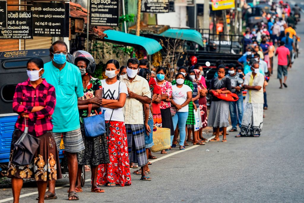 People wearing facemasks queue outside a shop at Pugoda on the outskirts of Sri Lanka's capital city Colombo. (Photo by ISHARA S. KODIKARA/AFP via Getty Images)