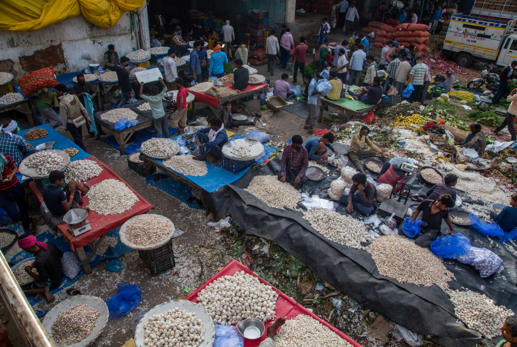 Indian shopkeepers and customers haggle  over the prices of fruits and vegetables in a crowded Mandi (market place), as nationwide lockdown continues over highly contagious novel coronavirus on March 26, 2020 in New Delhi, India. (Photo by Yawar Nazir/Getty Images)