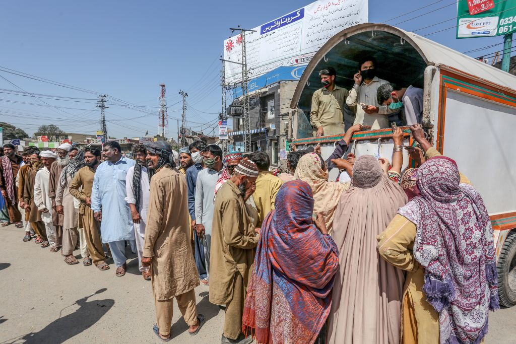 People queue to buy wheat bags at a government food distribution point duringa government-imposed nationwide lockdown as a preventive measure against the COVID-19 coronavirus, in Multan on March 28, 2020. (Photo by SHAHID SAEED MIRZA/AFP via Getty Images)