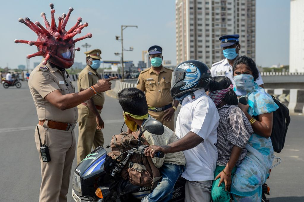 Police inspector Rajesh Babu (C) wearing coronavirus-themed helmet speaks to a family on a motorbike at a checkpoint during a government-imposed nationwide lockdown as a preventive measure against the COVID-19 coronavirus in Chennai on March 28, 2020.  (Photo by ARUN SANKAR/AFP via Getty Images)